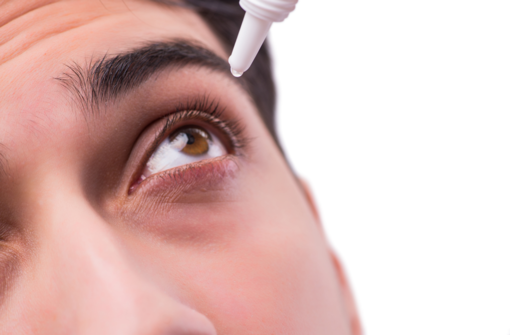 Man adding artificial tears to eye with dropper