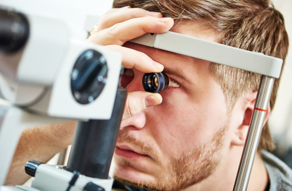 Man has left eye checked with loupe during his eye exam.