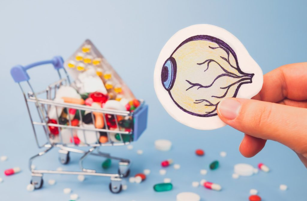 Hand holding drawing of eye in front of shopping cart filled with pills