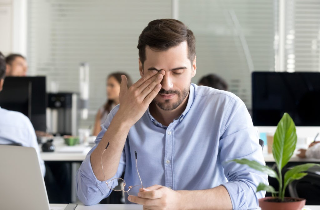 Young professional man frustrated due to dry eyes