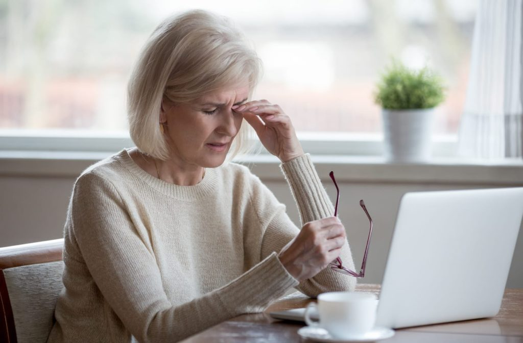 Older woman suffering from dry eye when using computer